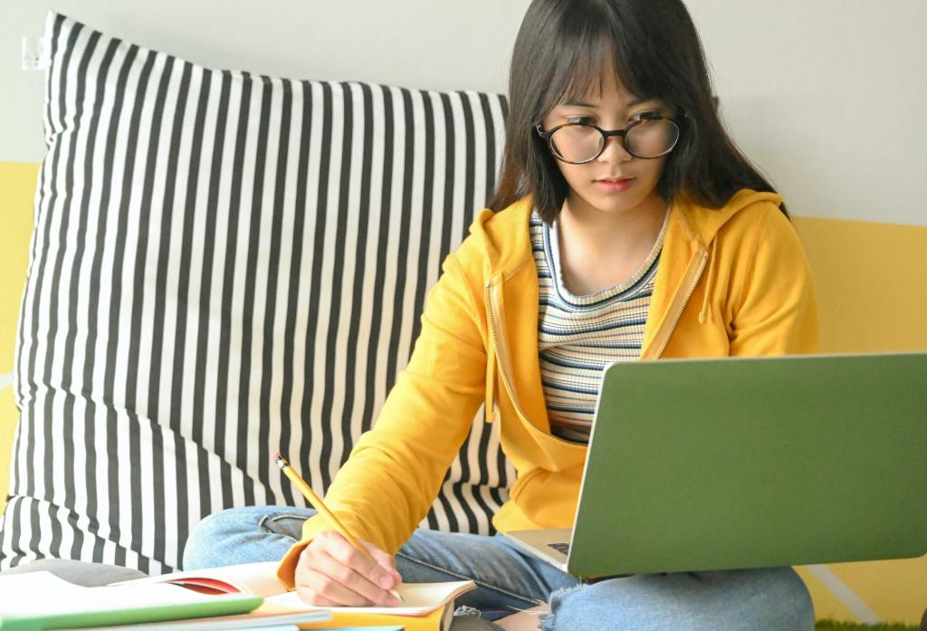 Asian female student wearing glasses is researching with a laptop and taking notes.