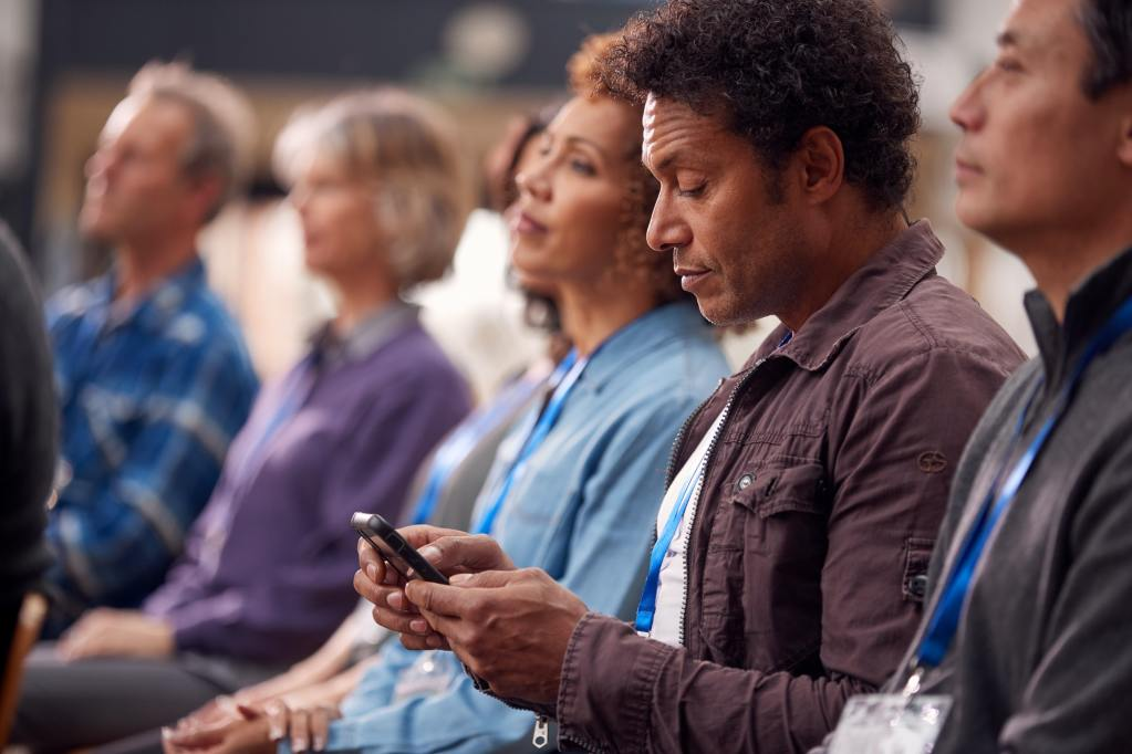 Businessman In Presentation At Conference Checking Mobile Phone