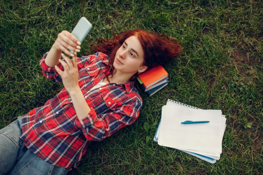 Female student with mobile phone lying on grass