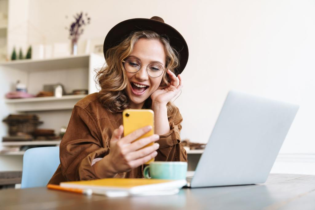 Image of cheerful young woman working with laptop and mobile phone