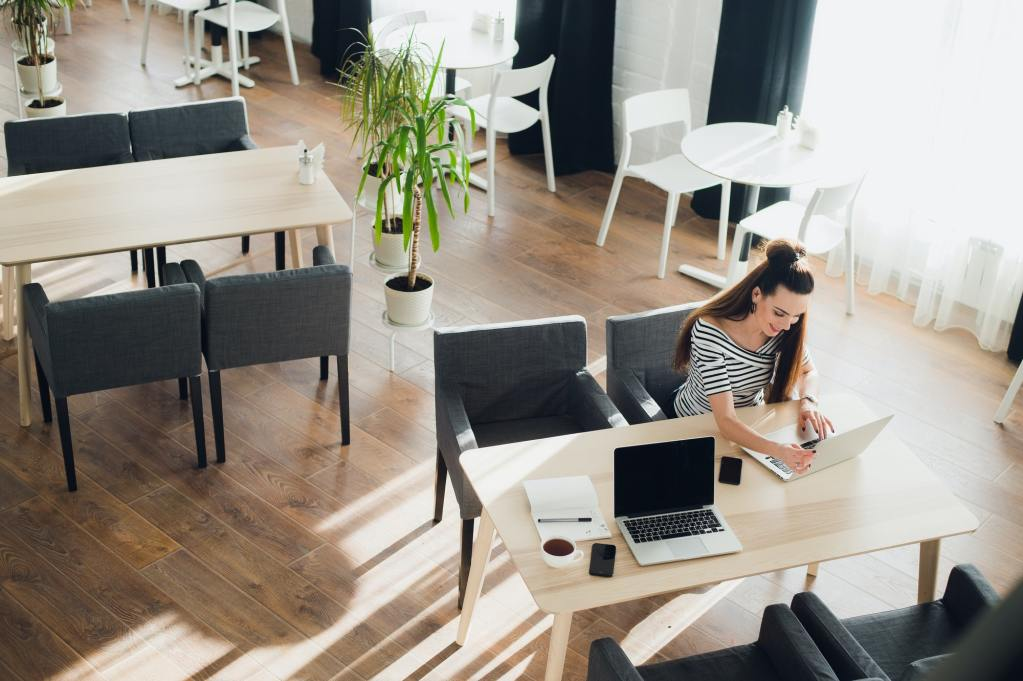 Side view. Young business woman sitting at table and taking notes in notebook. On table is laptop