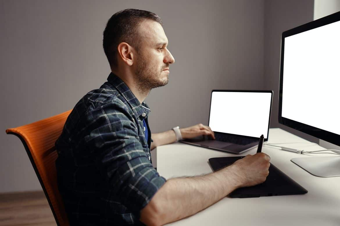 Young man working with interactive pen display and computer
