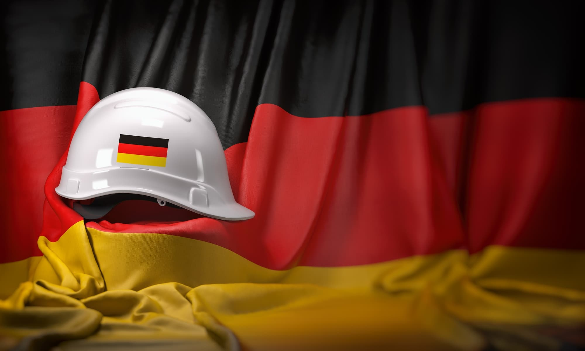 White hard hat laying over Germany flag. Construction and employ